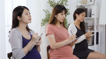 portrait of three asian expectant mothers participating antenatal group class in pleasant mood and sitting in bright classroom together.