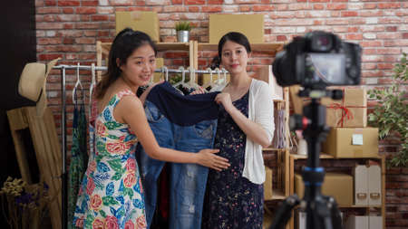 young charming asian chinese maternity lady seller with big belly selling jeans for pregnant woman customers. Stock fotó