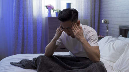illness asian guy sitting on bed is having bad headache, feeling stressful and rubbing his temples with both hands.
