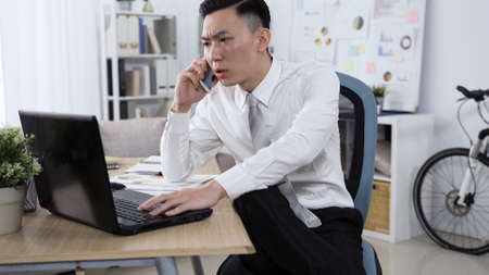 serious asian chinese guy sitting at desk, using laptop computer and talking on phone call with colleagues.