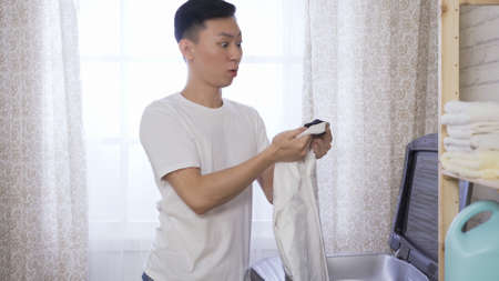 good user experience asian man satisfied with newly launched detergent after taking a white shirt out of machine.