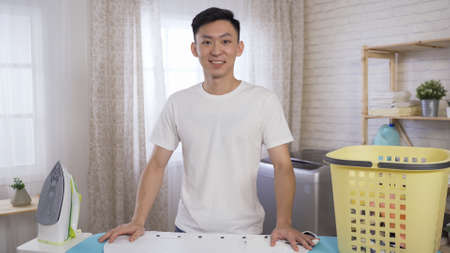 smiling asian korean male vlogger looking to camera while standing behind ironing board in bright room at home. Stock fotó - 163357618