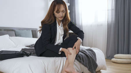 well-groomed lady sitting on hotel room bed is crossing leg and removing shoes, resting barefoot for comfort. woman rubbing her sore legs with uncomfortable look. genuine lifestyle
