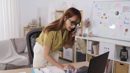 beautiful asian korean assistant standing behind laptop pc while confirming the appointment with her executive by cellphone. Stok Fotoğraf