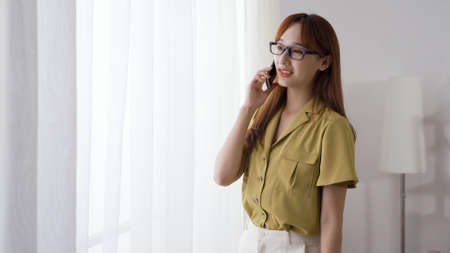charming asian taiwanese woman in glasses looking outside the window while speaking on phone and smiling.