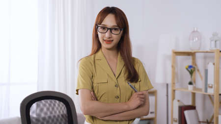 blurred background confident asian korean female ceo wearing glasses and holding pen while facing camera and standing with arms crossed. Stock fotó