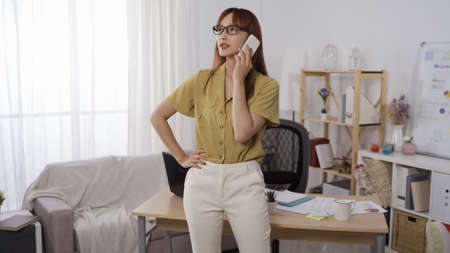 confident asian chinese businesswoman standing with one hand on waist and speaking on phone in her modern office.