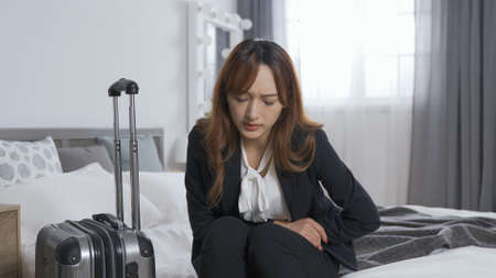 front view woman in formal wear sitting on hotel room bed with her luggage is having bad stomachache. getting sick during business trip concept. real moments Stok Fotoğraf