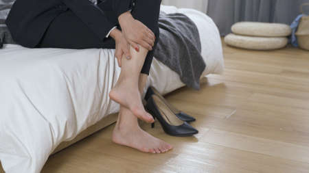 closeup view of businesswoman taking off high heel after work at home. lady in black pants massaging her foot to relive pain. occupational disease and health concept. authentic lifestyle