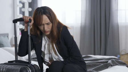lady in business suit seated on bed at home feeling extreme pain in her belly. woman grasping suitcase handle is having diarrhea before leaving for business trip in early morning