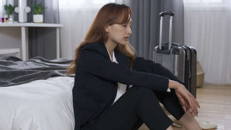 tired female entrepreneur sitting back against bed, covering her face in despair before another business trip. depression, wanting to escape from responsibility concept