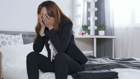female entrepreneur slapping down her bag on bed, sitting at bedside and covering face in frustration. feel like herself a loser at work concept