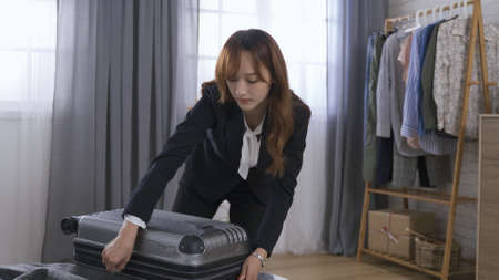 getting ready for business trip at home concept. korean businesswoman sliding up suitcase, heaving it down on the floor, drawing the handle and dragging it away. real moments Stok Fotoğraf