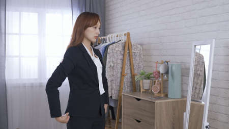 female ceo taking jacket from clothing rack, slipping on it while approaching to the mirror. lady in formal wear pulling out hair getting tucked underneath, arranging collar and doing up the button