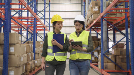 two asian chinese women managers in logistics industry talking about work with parcels placement in large warehouse