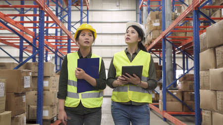 two asian japanese women industrial coworkers looking up forward together while working in logistic and shipment company. Stok Fotoğraf