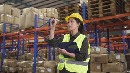 young concentrated asian korean woman warehouse worker holding clipboard and counting cardboard boxes in warehouse.