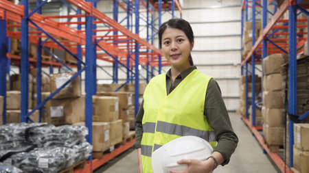 Portrait of smiling warehouse worker asian korean woman wearing safety vest and holding hard hat and looking in camera while standing in stockroom Stok Fotoğraf