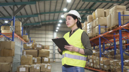 confident asian woman inventory manager standing in a large bright warehouse and working stock taking with touchpad.
