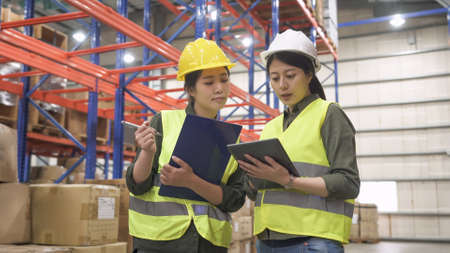 group of warehouse asian women staffs in hard hat and reflective jacket discussing work and walking in rows of shelves in the stockroom.