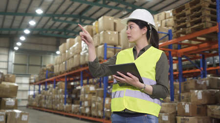 warehouse asian chinese lady manager in hard hat counting and using digital tablet while working in large in storehouse Stok Fotoğraf