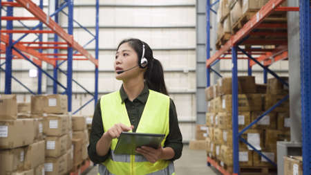 woman staff in reflective vest talking online phone call to help customers solving problem in storeroom with tablet