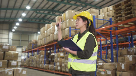young asian chinese woman pointing finger and checking list in documents on clipboard while working at large warehouse. Stok Fotoğraf