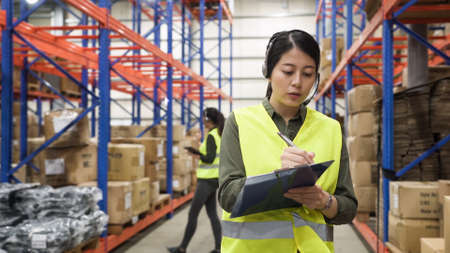 two young asian chinese girl customer service agent wearing headsets, talking online phone call and making note on clipboard in large distribution warehouse.
