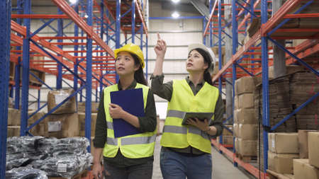 two industrial asian women coworkers looking up and pointing finger on shelves in logistic and shipping company.