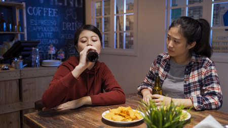 sad asian japanese woman feeling stressed and drinking beer in bar while worried girl friend consoling and looking at her in vintage club. Stok Fotoğraf
