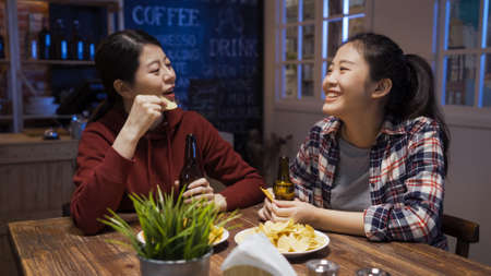 two happy young girl friends laughing and talking while sitting together in bar restaurant lounge at night