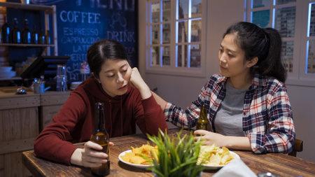 worried asian korean woman with bottles of beer cheering up her upset drunk friend in dark pub at night