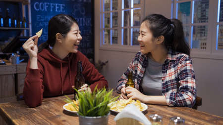 Cheerful lady friends drinking beer and eating chips together while having fun in free time at bar restaurant
