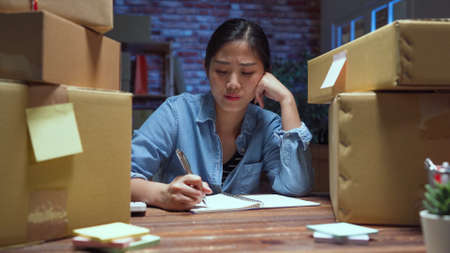 frowning young asian chinese woman worker unsuccess for work about online business and sitting at desk with cardboard boxes in late night office alone. Stok Fotoğraf