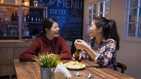 two excited happy female best friends having pleasant conversation and laughing at joke in night pub.