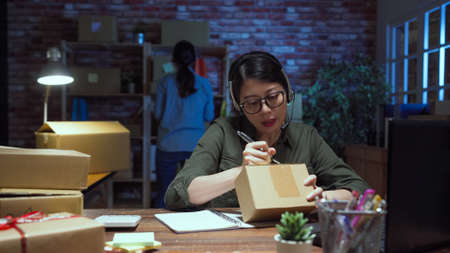 Support phone operator in headset talking to customer by microphone and making note on parcel while female coworker standing in back check cardboard box in dark office.