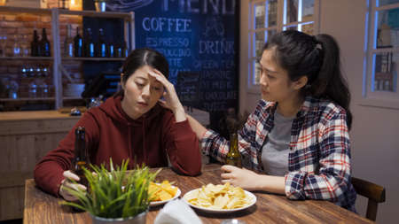 frowning asian chinese girl comforting sad best friend and touching her shoulder while drinking beer at night club.