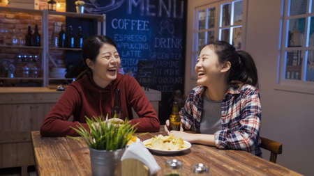group of young girl friends enjoy eating junk food and drinking alcohol in bar restaurant late night.