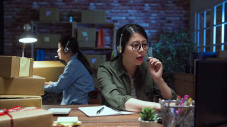 two asian chinese women customer support phone operators sitting at office and overtime working in midnight.