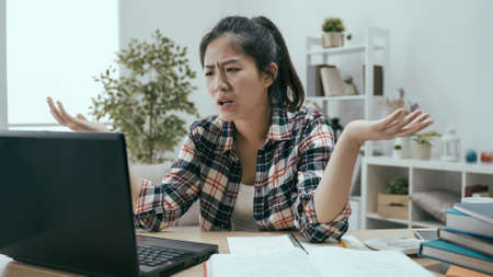 unhappy japanese university student throwing hands up for encountering unexpected problem on computer system on laptop.