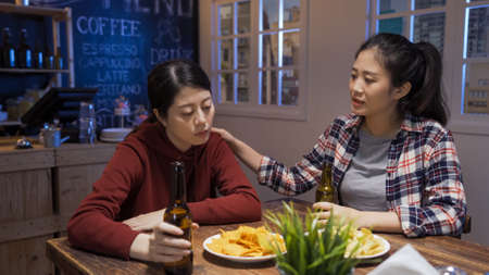 group of young ladies talking and comforting with beers and snacks on wooden table in dark pub at late midnight