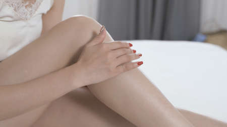 closeup elegant female's hand with nail art is gently rubbing lotion on her smooth leg back and forth. beauty and daily body care routine concept. seductive woman image