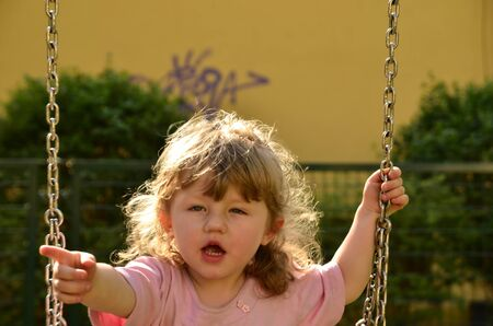 Photo shows a little girl on a swing at the playground in the park That shows who has her swing  Banco de Imagens