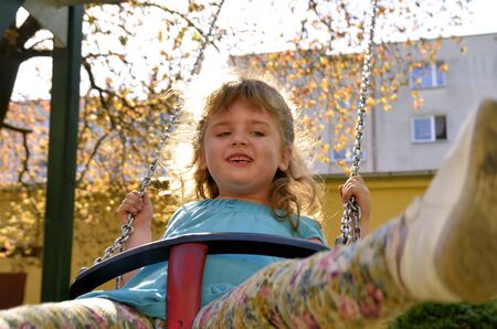 Photo shows a little girl on a swing at the playground in the park Banco de Imagens - 13664309