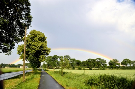 atmospheric phenomena: The photo shows a rainbow over the tops of trees growing next to the bike path and the rim of the field, after a sudden, torrential rain  Stock Photo