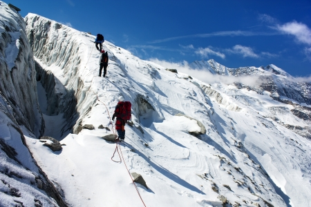 alpinism: group of climbers on rope on glacier - sunny day on mountain