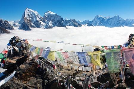 ri: view from Gokyo Ri to Arakam Tse, Cholatse, Tabuche Peak, Thamserku and Kangtega with prayer flags - trek to Everest base camp - Nepal