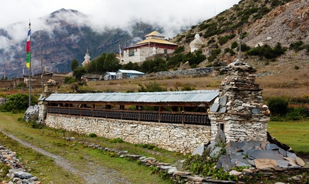 mani prayer wall with prayer wheels, gompa and stupas - annapurna trek - Nepa photo