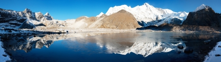 panoramatic: view of Cho Oyu mirroring in lake - Cho Oyu base camp - Everest trek - Nepal Stock Photo