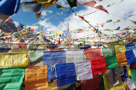 stupas: Prayer flags with stupas - Kunzum La pass - Himachal Pradesh - India  Stock Photo